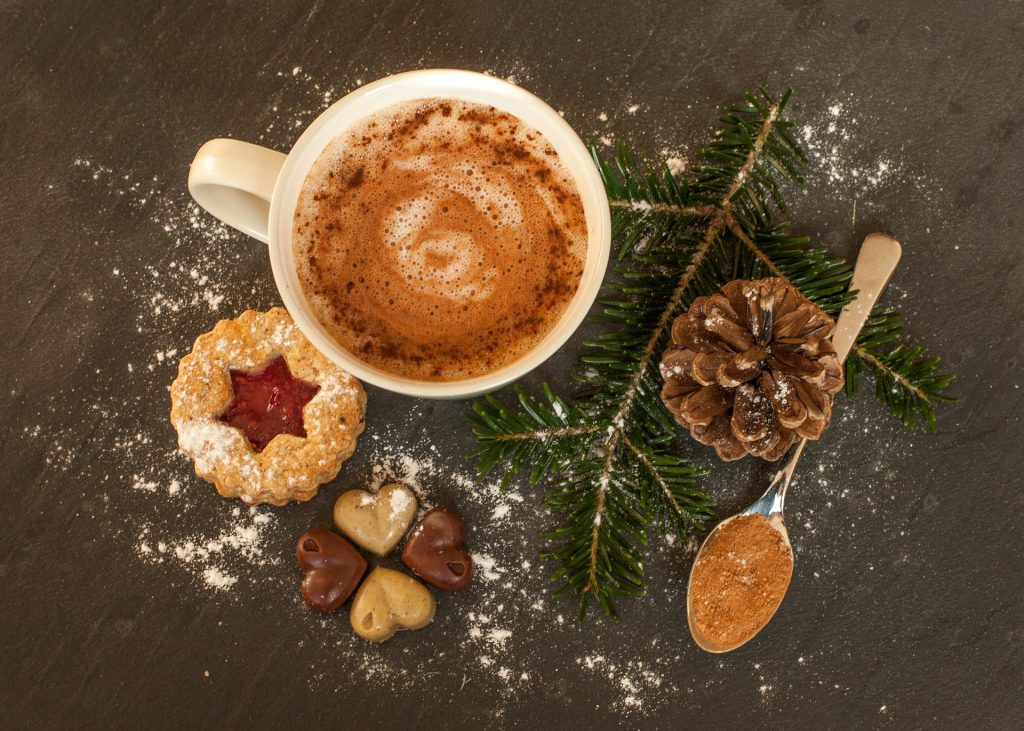 Overhead view of hot cocoa mug with pinecone and cookies